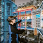 An industrial engineer takes measurements of its industrial plant.